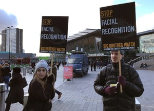 In this Feb. 11, 2020, photo, Silkie Carlo, left, demonstrates in front of a mobile police facial recognition facility outside a shopping centre in London. Image: AP Photo/Kelvin Chan