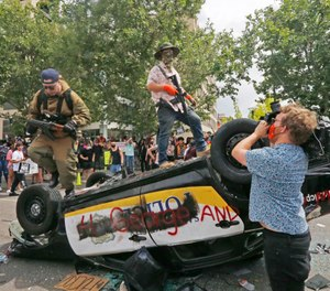 Armed protesters climb on a flipped over police vehicle Saturday, May 30, 2020, in Salt Lake City. (AP Photo/Rick Bowmer)