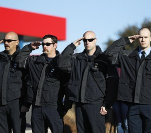 First responders salute as Lubbock Police Officer Nicholas Reyna and Lieutenant/Paramedic Eric Hill are transported to the County Medical Examiner's Office in Fort Worth, Texas. Reyna and Hill died after a vehicle collided with them while responding to an accident on Interstate 27.