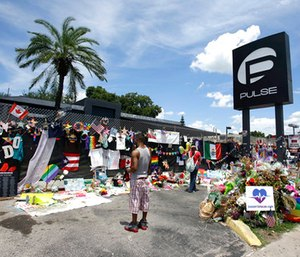 Visitors gather at a makeshift memorial outside the Pulse nightclub in Orlando, Fla.