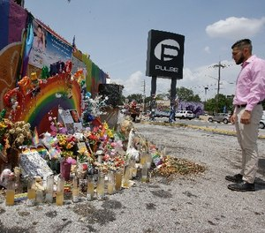 In this Tuesday, May 30, 2017 photo, Marco Quiroga, who works to support LGBTQ and social-justice causes in central Florida, reflects in front of one of the memorials at the Pulse Nightclub in Orlando, Fla. (AP Photo/John Raoux)