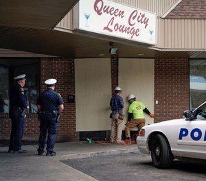 Police officers watch as workers board up the Queen City Lounge in Cincinnati, Ohio. (Photo/TNS)