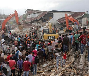 Rescuers use excavators to search for victims under the rubble of collapsed buildings after an earthquake in Pidie Jaya, Aceh province, Indonesia. (AP Photo/Heri Juanda)