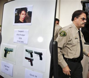 In this May 24, 2014, file photo, Santa Barbara County Sheriff Bill Brown, right, walks past a board showing the photos of gunman Elliot Rodger.