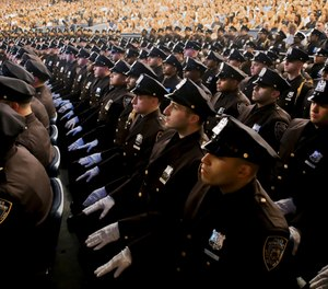 Members of New York Police Academy's July 2018 graduating class of 726 new NYPD police officers from more than 41 countries, show their white-gloved hands while seated during graduation ceremony, Monday July 2, 2018, in New York. (AP Photo/Bebeto Matthews)