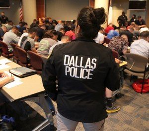 Potential police recruits take a test during an applicant processing event at police headquarters in Dallas, Thursday, Sept. 7, 2017.
