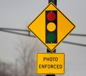 In this Tuesday, Feb. 10, 2015 file photo, a sign warns motorists of the presence of a red light camera in Chicago. (AP Photo/M. Spencer Green, File)