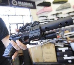 Jordan Baylon, 22, holds a realistic-looking air gun.