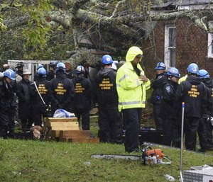 Rescue workers, police and fire department members wait to remove the bodies of a mother and child who were killed by a falling tree as Hurricane Florence made landfall in Wilmington, N.C. (Photo/AP)