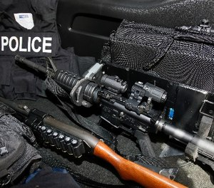 An AR-15 rifle, a shotgun, a vest and other safety gear is pictured in a police patrol car in Edmond, Okla., Thursday, July 14, 2016.