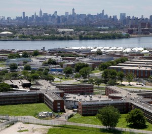 This June 20, 2014 file photo shows the Rikers Island jail complex in New York with the Manhattan skyline in the background. (AP Photo/Seth Wenig, File)