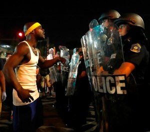A man yells at police in riot gear just before a crowd turned violent Saturday, Sept. 16, 2017, in University City, Mo. (AP Photo/Jeff Roberson)