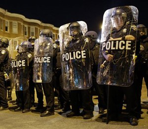 Police stand in formation as a curfew approaches in Baltimore, April 2015.
