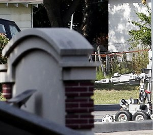 A bomb disposal robot inspects the area surrounding a armored van, top left of frame, during a stand off with a gunman barricaded inside the van, Saturday, June 13, 2015, in Hutchins, Texas.