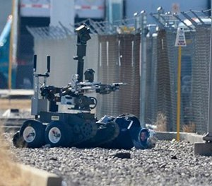 A bank robbery suspect wearing a motorcycle helmet lies handcuffed on the ground as a bomb squad robot searches his vest. (AP Image)