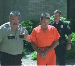 In this May 1999 file photo, Polk County Sheriff's officer and a member of the Mena Police Department lead Karl Roberts from the Polk County Detention Center to the Polk County Courthouse. (Photo/TNS)