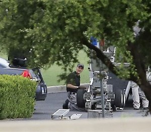 File Photo - Police appear to set up a remotely operated robot during a stand off with a gunman on June 13, 2015 in Hutchins, Texas. (AP Images)