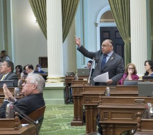 California Assemblyman and former EMT Freddie Rodriguez (standing) welcomes guests to the state capitol during EMS Week in 2019. Rodriguez has introduced a legislation package aimed at increasing regulations to improve work conditions at private ambulance services. (Photo/Assemblyman Freddie Rodriguez)