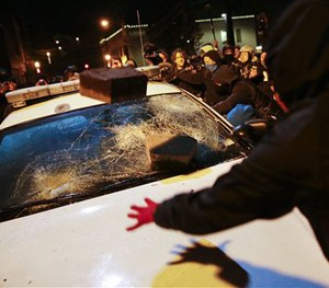 Protesters vandalize a police vehicle outside of the Ferguson city hall in Tuesday, Nov. 25, 2014, in Ferguson, Mo.