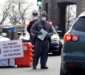 Police officers direct drivers as they enter Glen Island Park in New Rochelle, N.Y. on March 22, 2020. The park was the first COVID-19 testing site in Westchester County.