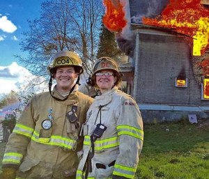 Ramsey Mueller and his mother, Deputy Chief Faith Mueller, stand in front of a controlled training burn on March 26, 2016. (Photo/Tacoma Fire Department)