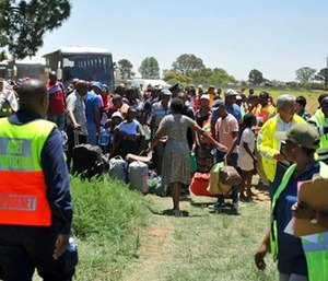 Train passengers are transferred to a bus at the scene of a train accident near Kroonstad, South Africa.