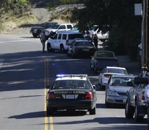 A California Highway Patrol car and other law enforcement vehicles set up a roadblock near Placer High School leading to a rural area where authorities are searching for an assailant, in Auburn, Calif., who shot three sheriff's deputies in two Northern California Counties, Friday, Oct. 24, 2014.