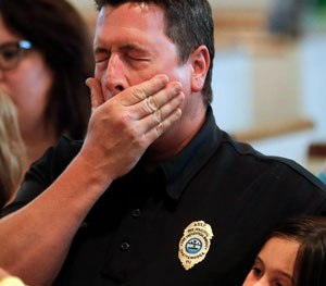 Chuck Hartung holds his daughter Haley, 8, during a prayer service at Wesley Memorial United Methodist Church for the victims of shootings. (AP Image)