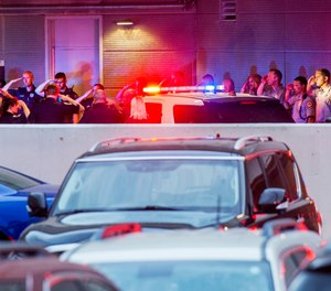 In this Tuesday, June 25, 2019 photo, law enforcement officers from numerous jurisdictions in central Illinois salute at the emergency entrance at OSF Saint Francis Medical Center in Peoria, Ill. (David Zalaznik/Journal Star via AP)