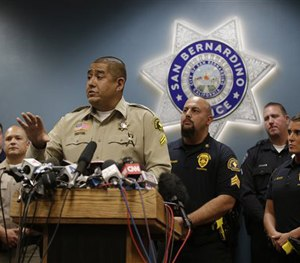 San Bernardino County Sheriff's detective Jorge Lozano, center, answers questions from reporters during a news conference.