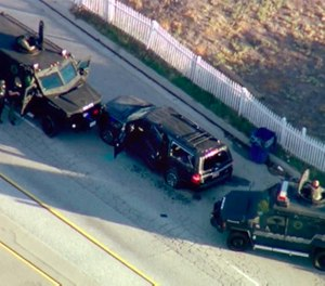 In this Dec. 2, 2015, file image, taken from video, armored vehicles surround an SUV following a shootout in San Bernardino, Calif. (KTTV via AP, File)