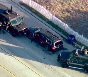 In this Dec. 2, 2015, file image, taken from video, armored vehicles surround an SUV following a shootout in San Bernardino, Calif.