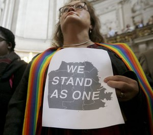 The Rev. Annie Steinberg-Behrman holds a sign while listening to speakers at a meeting at City Hall in San Francisco by city leaders and community activists to reaffirm the city's commitment to being a sanctuary city Monday, Nov. 14, 2016. (AP Photo/Jeff Chiu)