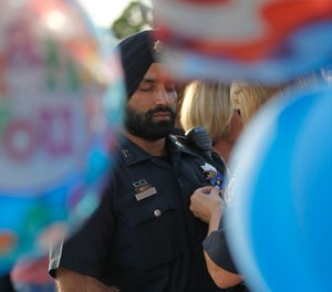 In this Aug. 29, 2015, photo, Harris County Sheriffs deputy Sandeep Dhaliwal gets a blue ribbon pinned to him during a vigil at the Chevron station in Houston, where Harris County deputy Darren Goforth was shot and killed previous night while he was refueling his vehicle. (Karen Warren/Houston Chronicle via AP)
