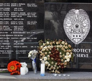 Flowers and candles were left at the San Diego Police Department memorial to officers who died in the line of duty the morning after an officer-involved shooting left one officer dead and one wounded. (John Gastaldo/The San Diego Union-Tribune via AP)