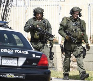 San Diego Police SWAT officers walk down the street after entering a house with a possible suspect inside Friday, July 29, 2016, in San Diego. (AP Photo/Denis Poroy)