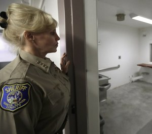 In this photo taken on Monday, Dec. 16, 2019, Santa Clara County Sheriff Laurie Smith looks into a solitary confinement cell designed for a disabled inmate at the Main Jail in San Jose, Calif. (Photo/Ben Margot/AP)