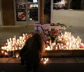 A woman places a candle in front of IV Deli Mart, where par of Friday night's mass shooting took place by a drive-by shooter, on Saturday, May 24, 2014, in the beach community of Isla Vista, Calif.