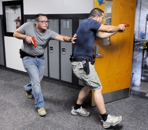 Justin Royse, left, and Dakota Steele practice moving down a hallway during active shooter training at Daleville High School in Daleville, Ind. on Saturday, June 23, 2018. (Don Knight)/The Herald-Bulletin via AP)