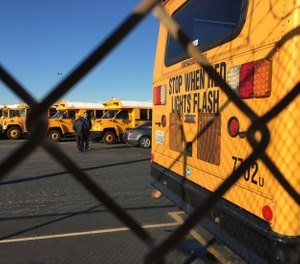 Los Angeles Unified School District buses stand idle in Gardena, Calif., on Tuesday, Dec. 15, 2015. (AP Photo/Damian Dovarganes)