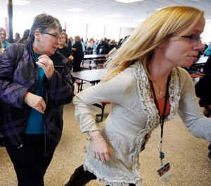 Participants rush out of the cafeteria after hearing gun shots during a lockdown exercise at Milford High School in Milford, Mass. (AP Photo/Michael Dwyer, File)