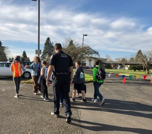 Eugene police officers and teachers escort students at Cascade Middle School in Eugene, Ore., Friday, Jan. 11, 2019.