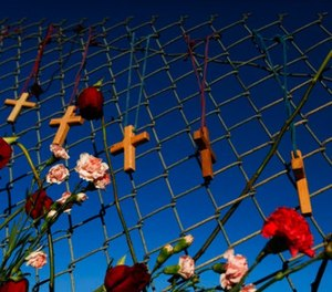 Crosses and flowers hang on a fence near Marjory Stoneman Douglas in Parkland, Fla., on Saturday, Feb. 16, 2018, in memory of the 17 people killed in a school shooting on Wednesday.