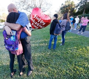 Family member embrace following a shooting at Marjory Stoneman Douglas High School, Wednesday, Feb. 14, 2018, in Parkland, Fla.