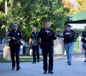 Santa Rosa police officers carry guns as they search the campus of Ridgway High School for suspects after a shooting at the school. (Beth Schlanker/The Press Democrat via AP)