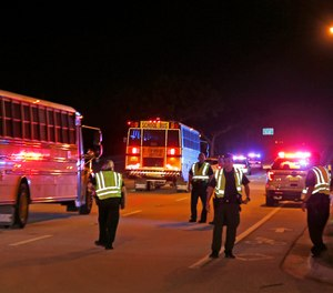 Police officers stand watch as spectators are bussed from a shooting incident at a practice football game between Dwyer and Palm Beach Central High School Friday, Aug. 17, 2018, in Wellington, Fla.