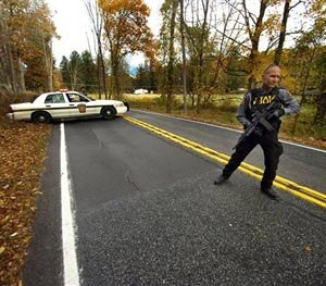 A Pennsylvania State Trooper patrols along a closed section of Lower Swiftwater Road on Saturday, Oct. 18, 2014, during a massive manhunt for killer Eric Frein in Swiftwater, Pa. (AP Image)