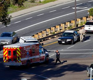 A law enforcement officer directs an ambulance near the Naval Medical Center San Diego following a report of gunshots. (Nelvin C. Cepeda /The San Diego Union-Tribune via AP)