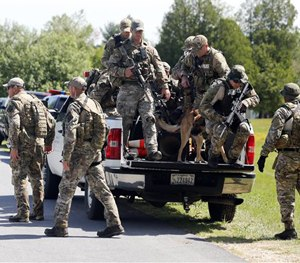 Law enforcement officers get off a truck as they return to their vehicles after searching a wooded area on Sunday, June 14, 2015.