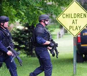 Two law enforcement officers make their way across a lawn and onto Pleasant Street on Wednesday, June 10, 2015 in Dannemora, N.Y. (AP Image)